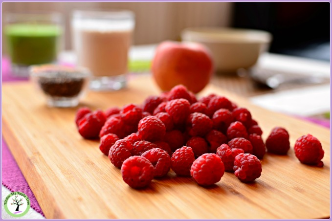 Ingredients for a delicious raspberry smoothie: fresh raspberries, almond milk, one apple and chia seeds.