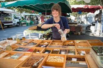Emilie Philippin from Le Baluchon. Dried fruit and nuts retailer, here in Carouge market. Image by Carole Parodi, (c) karibou.ch